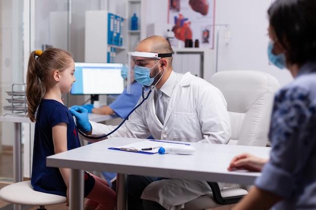Criança olhando para o médico especialista enquanto ouve o coração com estetoscópio para exame médico. médico pediatra com luvas de proteção e máscara contra covid19 falando sobre tratamento de doenças