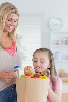 Criança olhando para saco de supermercado
