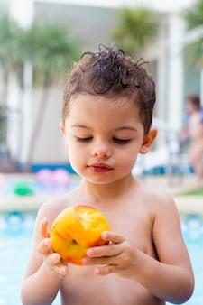 Criança olhando para um pêssego mordido, ele está segurando na mão dentro de uma piscina