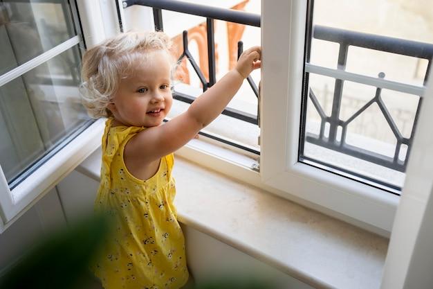 Criança olhando pela janela durante a quarentena Foto gratuita