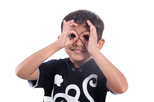 Criança olhando por entre os dedos em gesto de ok. binóculos imitando