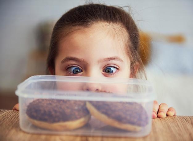 Criança olhando rosquinhas deliciosas Foto gratuita