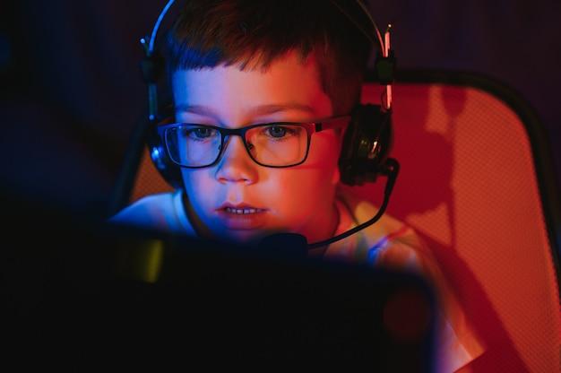 Criança online transmite jogo de computador, menino transmite em fones de ouvido no fundo de iluminação rgb