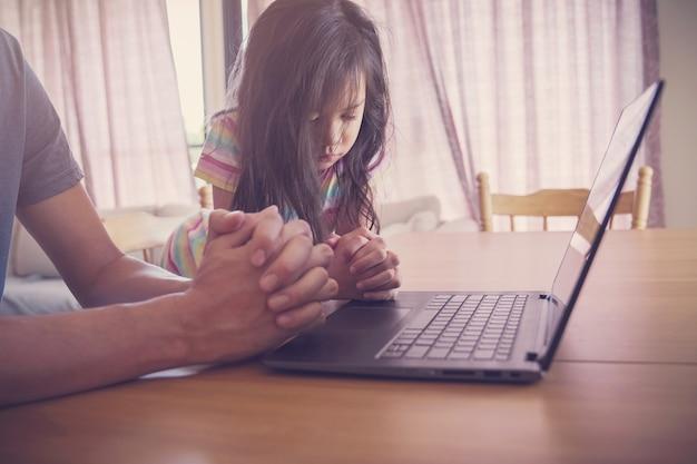 Criança orando com pai e mãe com laptop, família e filhos orando online em casa