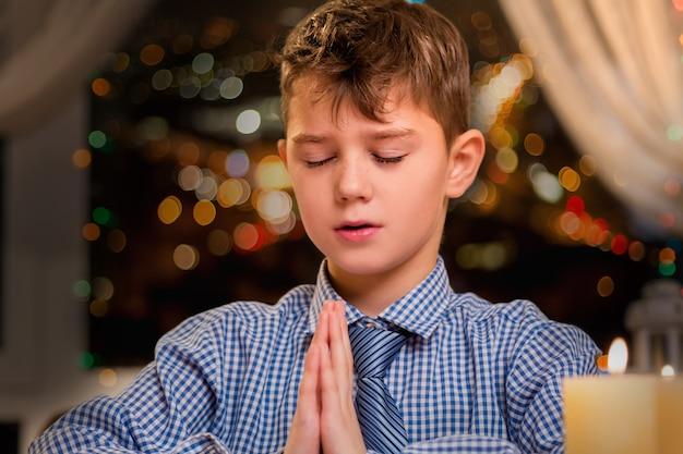 Criança orando em voz alta. menino orando à luz de velas. ele fala com o senhor. jovem, mas com uma fé forte.