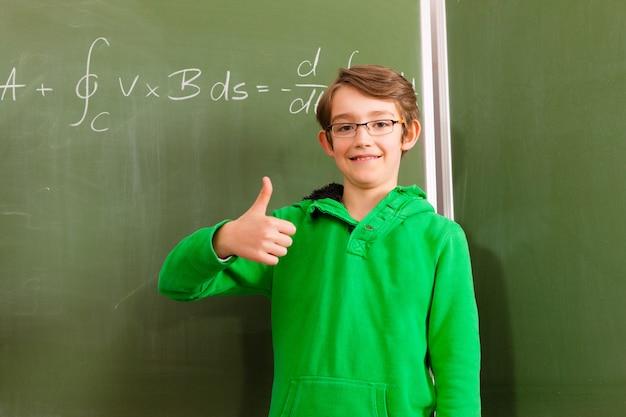 Criança ou aluno no quadro-negro na escola