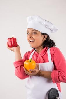 Criança ou menina indiana bonitinha vestida de chef e segurando utensílios de cozinha ou vegetais, isolada sobre um fundo branco