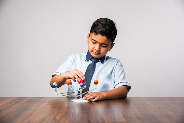 Criança ou menino indiano da escola estudando planetas ou ciências planetárias com o modelo 3d do nosso sistema solar