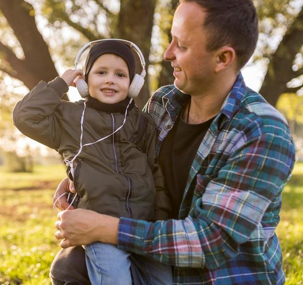 Criança ouvindo música e sendo abraçada pelo pai