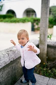 Criança parada no quintal em um ladrilho em frente a uma cerca baixa de pedra, mostrando a língua