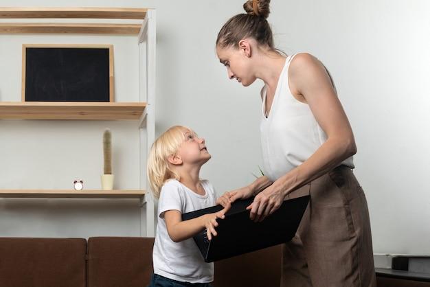 Criança pede laptop de sua mãe. rapaz tentando pegar o laptop das mães.