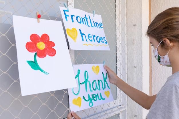 Criança pendurando mensagens positivas para heróis da linha de frente que trabalham durante a quarentena de coronavírus (covid-19).