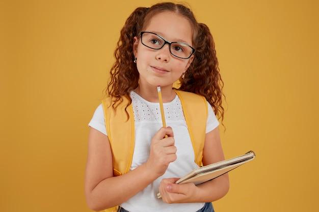 Criança pensando e segurando um caderno