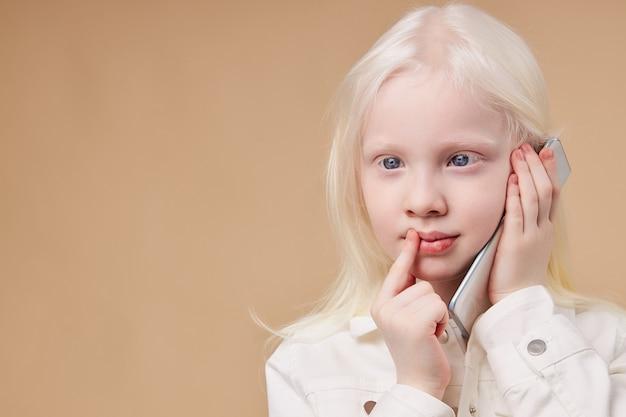 Criança pensativa e sonhadora com síndrome de albinismo falando ao telefone