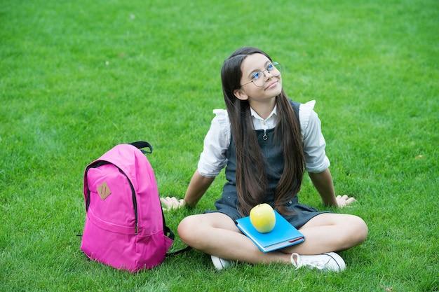 Criança pensativa em uniforme formal com livro e maçã lanche escolar saudável relaxar na grama verde, lanches.