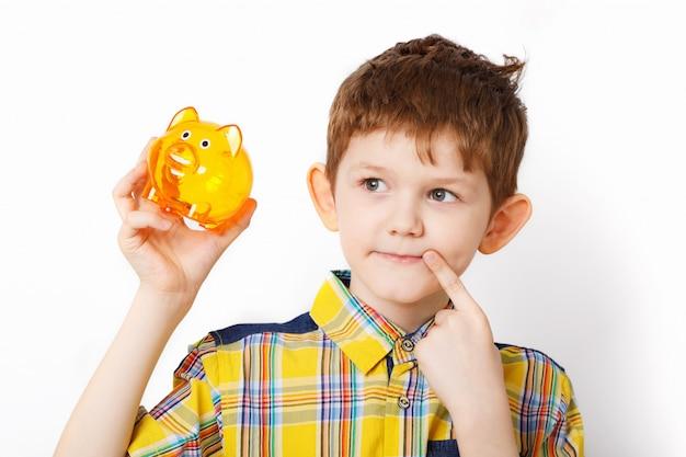 Criança pensativa, segurando um cofrinho.