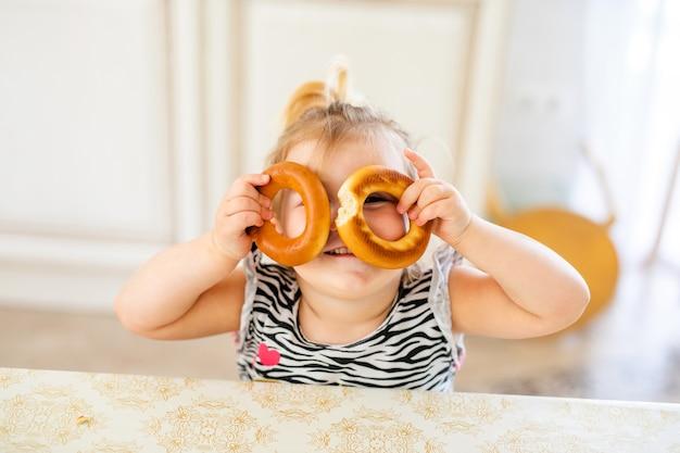 Criança pequena almoçando na cozinha quente e ensolarada. menina loira com rabo de cavalo engraçado brincando com dois deliciosos bagels.