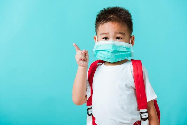Criança pequena asiática menino jardim de infância usar máscara protetora e saco de escola, apontando para o lado