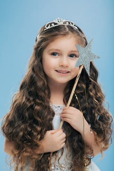 Criança pequena atraente, com cabelos escuros encaracolados, segura a varinha mágica