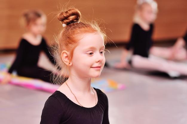 Criança - pequena bailarina ruiva linda garota realiza exercícios de alongamento na escola de balé