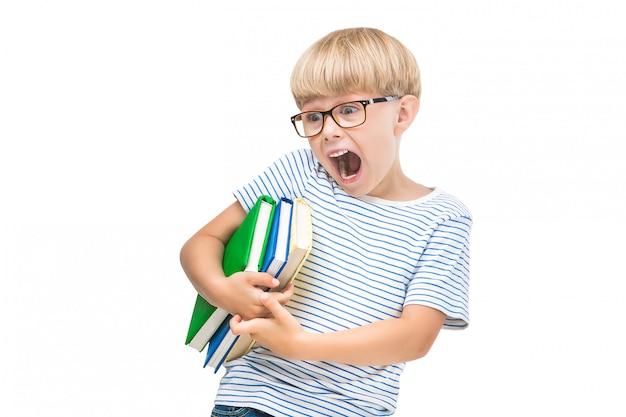 Criança pequena bonita com livros e cadernos leitura de criança adorável. foto de estúdio de estudante. rapaz usando óculos.