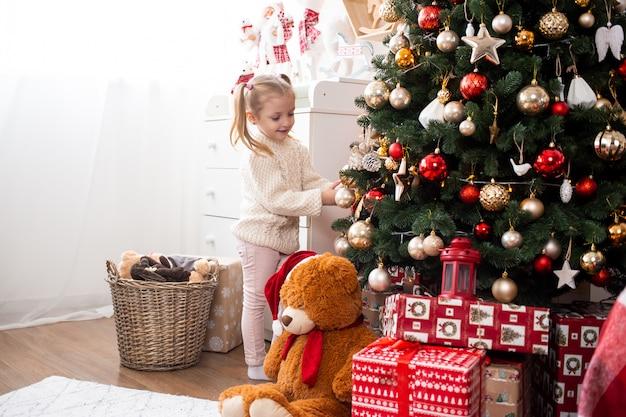 Criança pequena bonita decora a árvore de natal em casa