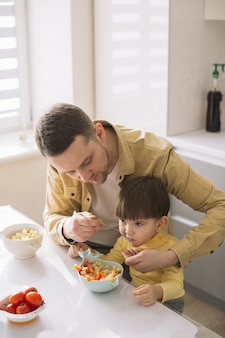Criança pequena bonita e seu pai comendo vista alta