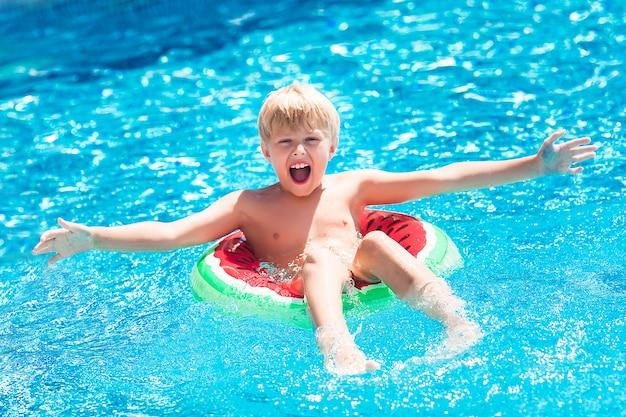 Criança pequena bonitinha na piscina. garoto engraçado nadando.