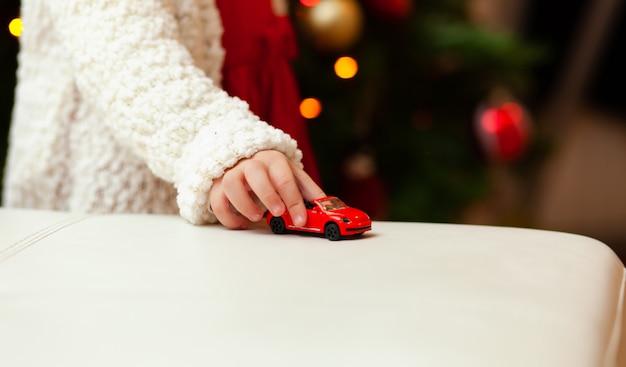 Criança pequena brinca com o carro de brinquedo pequeno.
