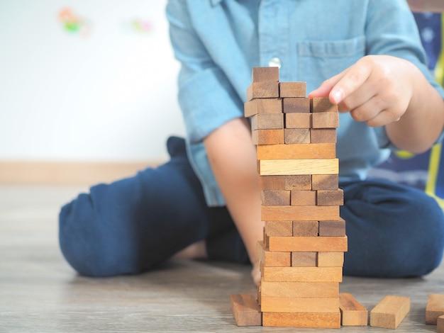 Criança pequena brincando com blocos de madeira no chão