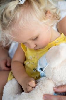 Criança pequena brincando com um brinquedo com máscara médica Foto gratuita