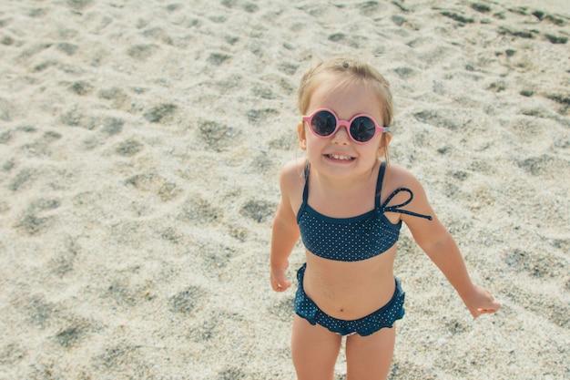 Criança pequena caminha na praia. garota de biquíni azul e óculos redondos em uma viagem
