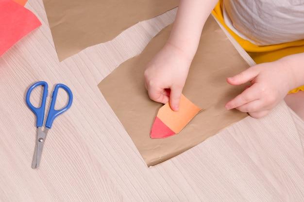 Criança pequena cola uma casa de papel, tesouras de segurança para crianças em uma mesa de madeira, o que fazer com a criança em casa, espaço de cópia, mãos das crianças sobre a mesa