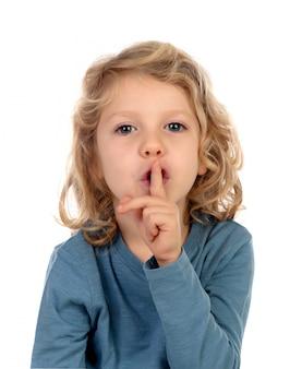 Criança pequena, colocando o dedo indicador aos lábios como sinal de silêncio