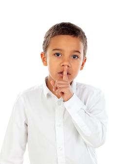 Criança pequena colocou o dedo indicador nos lábios como sinal de silêncio