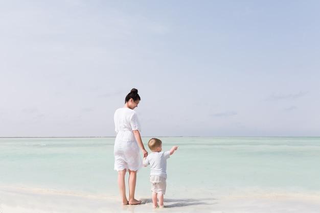 Criança pequena com a mãe na praia