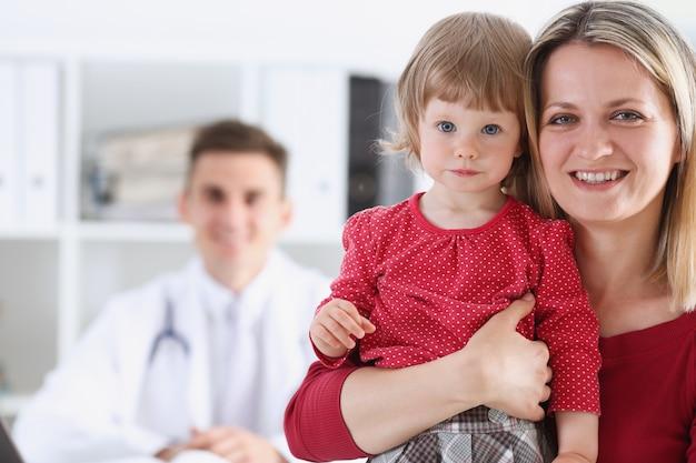 Criança pequena com a mãe na recepção do pediatra