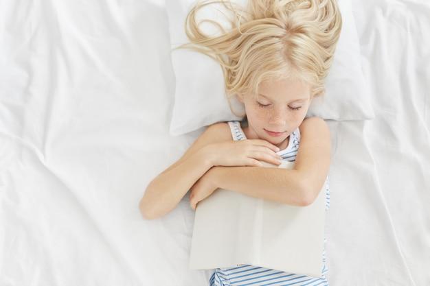 Criança pequena com aparência bonita dormindo depois de ler histórias interessantes na cama, mantendo o livro nas mãos, deitado no travesseiro branco e roupas de cama, tendo sonhos agradáveis. lendo antes de dormir