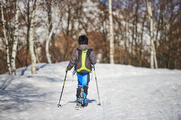 Criança pequena com esquis de turismo em estrada com neve