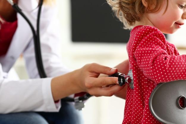 Criança pequena com estetoscópio na recepção do médico