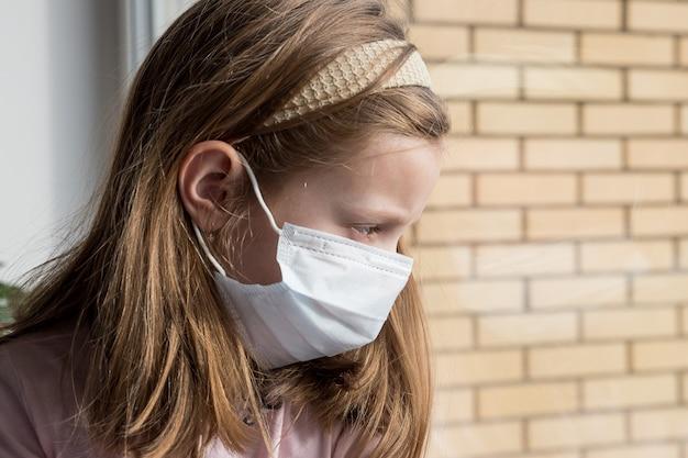 Criança pequena com máscara cirúrgica, olhando pela janela