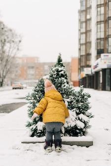 Criança pequena com roupa amarela em um dia de neve lá fora com um pinheiro coberto de neve