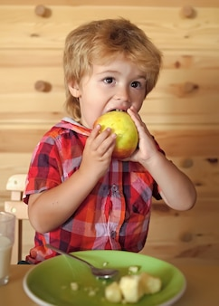 Criança pequena come maçã. alimentos e vitaminas para crianças saudáveis. café da manhã, família matinal.
