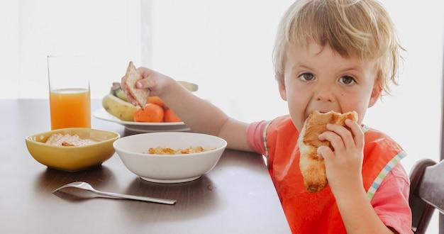 Criança pequena comendo croissant no café da manhã