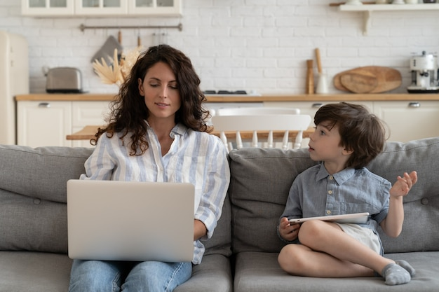 Criança pequena conversa com a mãe ocupada digitando no laptop, fazendo várias tarefas, mãe empresária trabalhando em casa com o filho