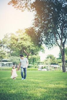 Criança pequena de mãos dadas com o pai no parque, o tempo de felicidade.
