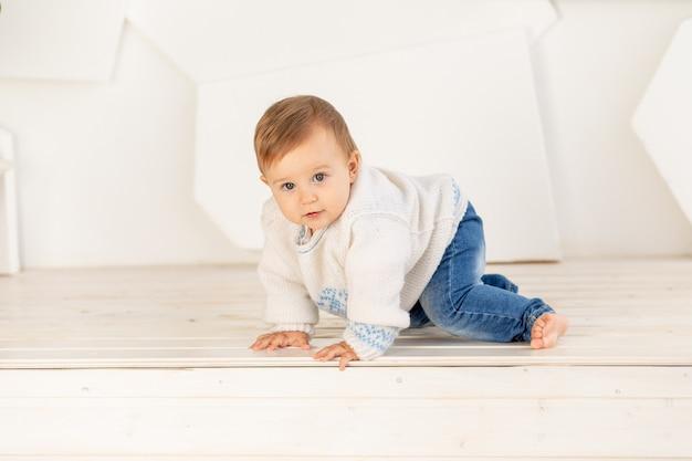 Criança pequena de seis meses em uma jaqueta quente de tricô e calça jeans rasteja em casa em uma sala iluminada