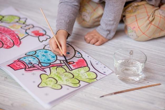 Criança pequena desenha coloração de água com pincel em casa