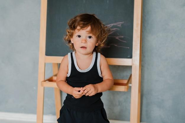 Criança pequena desenha com giz em um quadro de giz preto em casa no berçário contra uma parede cinza.