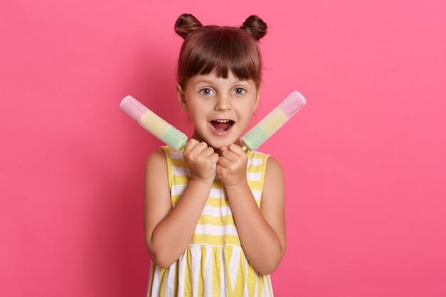 Criança pequena do sexo feminino segurando sorvete de duas frutas, garota encantadora com a boca bem aberta, usando um vestido de verão, parece animada, se divertindo com uma sobremesa deliciosa.